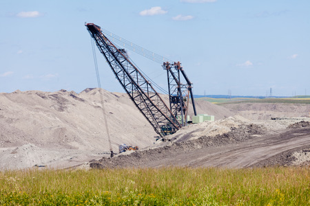 Coal mine industrial excavator machinery equipment among moon-like tailings landscape in Alberta, Canada photo