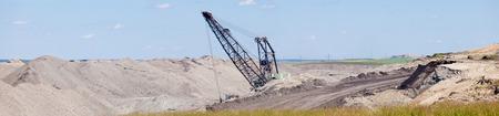 Coal mine industrial excavator machinery equipment among moon-like tailings landscape panorama in Alberta, Canada photo