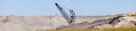 pile engine: Coal mine industrial excavator machinery equipment among moon-like tailings landscape panorama in Alberta, Canada