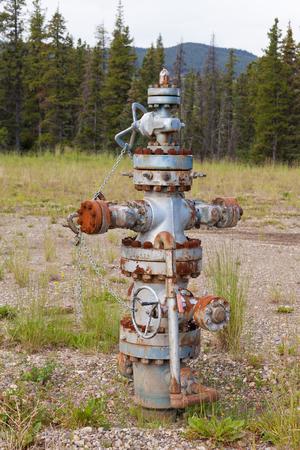 wellhead: Inoperational oil and gas petroleum industry wellhead flange gear locked shut, Alberta, Canada