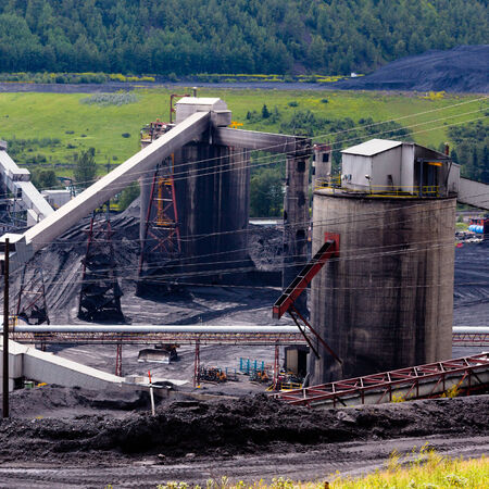 resource: Detail of coal mine black dirty building between piles of coal fossil energy fuel resource from active mining