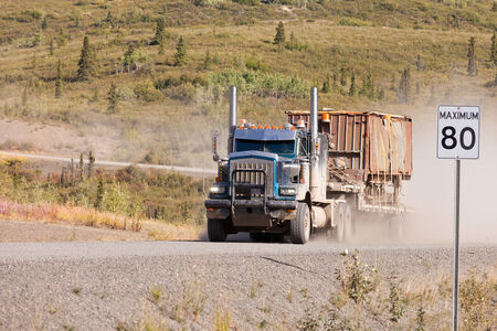 flatbed truck: Heavy duty articulated industrial truck drives fast on remote gravel road throwing up dust