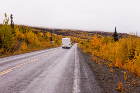 yukon territory: Camper van drives on highway with autumn or fall colorful yellow foliage of boreal forest taiga of yukon Territory, Canada Stock Photo