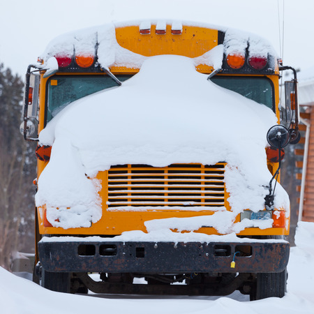 Snow covered front of parked school bus after heavy winter blizzard snow fall