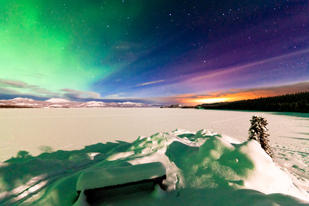 Spectacular display of Northern Lights or Aurora borealis or polar lights and light pollution from itself not visible city of Whitehorse over frozen Lake Laberge, Yukon Territory, Canada, moon-lit winter landscape