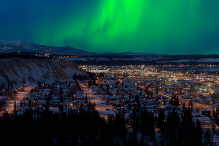 Strong northern lights Aurora borealis substorm on night sky over downtown Whitehorse, capital of the Yukon Territory, Canada, in winter. Banco de Imagens
