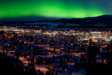 Sterke noordelijke lichten Aurora borealis substorm op nachtelijke hemel boven het centrum van Whitehorse, de hoofdstad van de Yukon Territory, Canada, in de winter.