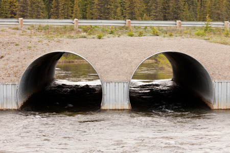 catchment: Road over dual culvert pipe infrastructure bridge strong current flow of river water tunnel through