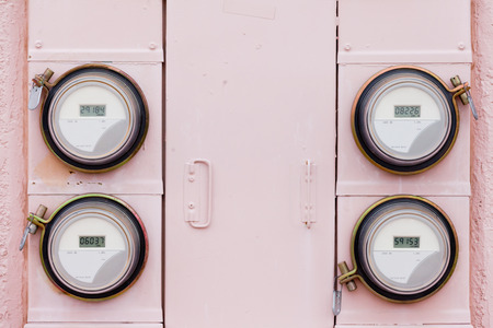 Array of four modern smart grid residential digital power supply watthour meters on grungy pink exterior wall