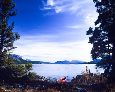 yukon territory: Red canoe on boreal forest taiga wilderness shore of beautiful calm Tagish Lake, Yukon Territory, Canada