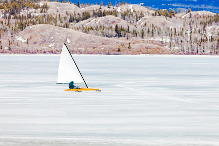 yachtsman: Sailing an ice-boat on ice surface of frozen Lake Laberge, Yukon Territory, Canada, driven on metal runner skids