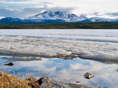 yukon: Spring break-up at Fox Lake, Yukon Territory, Canada, still snowy Little Peak reflection on open shore water and rock mimicking a small mountain