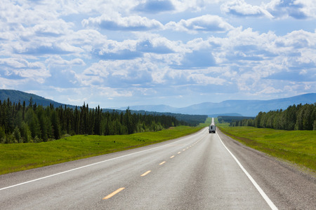 Recreational Vehicle RV southbound on empty road of Alaska Highway, Alcan, in boreal forest taiga landscape south of Fort Nelson, British Columbia, Canada Stock Photo