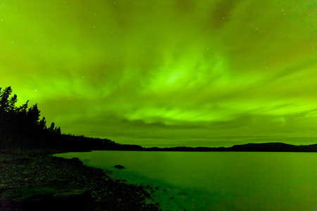 canada: Green sparkling show of Aurora borealis or Northern Lights on night sky over winter scene landscape of Lake Laberge, Yukon Territory, Canada