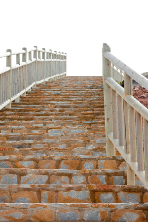 hand rails: View from the bottom of a steep flight of brick steps with wooden railings leading up to the skyline