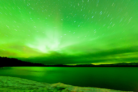 yukon: Green sparkling show of Aurora borealis or Northern Lights on night sky over winter scene landscape of Lake Laberge, Yukon Territory, Canada