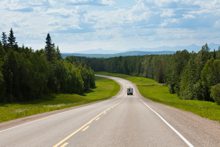 Recreational Vehicle RV on empty road of Alaska Highway, Alcan, in boreal forest taiga landscape south of Fort Nelson, British Columbia, Canada Stockfoto
