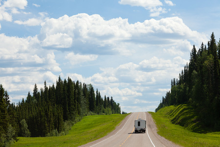 Recreational Vehicle RV on empty road of Alaska Highway, Alcan, in boreal forest taiga landscape south of Fort Nelson, British Columbia, Canada Stock Photo