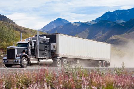 Heavy duty semi-truck met geladen container rijdt snel op onverharde weg in landelijke berglandschap overgeven stof Stockfoto