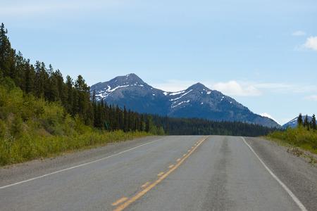 yukon territory: Mountainous wilderness surrounds Alaska Highway at km 1290 north of Teslin, Yukon Territory, Canada Stock Photo