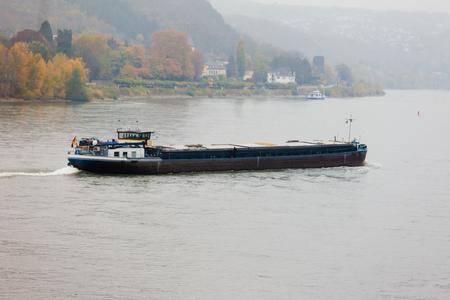 rhine westphalia: Inland cargo vessel barge on waterway river Rhine with autumn fall colored landscape on shore, North Rhine-Westphalia, Germany, Europe