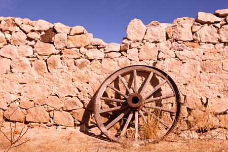 carreta madera: Hist�rico de la rueda de carro de madera apoyado contra la pared rota de piedras naturales como una reliquia de la historia del oeste salvaje en el oeste de Texas, EE.UU.