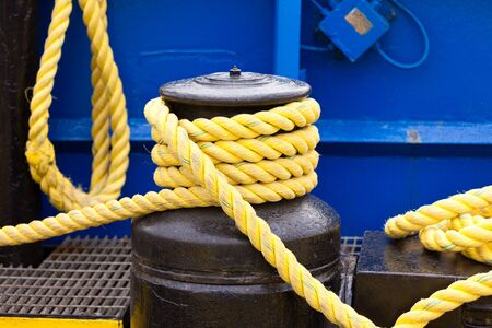 winch: Yellow mooring line coils on black winch marine ship equipment detail