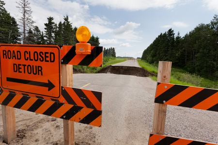 road closed: Road closed detour sign on blocked washed out road with rain flood washout damaged broken asphalt Stock Photo