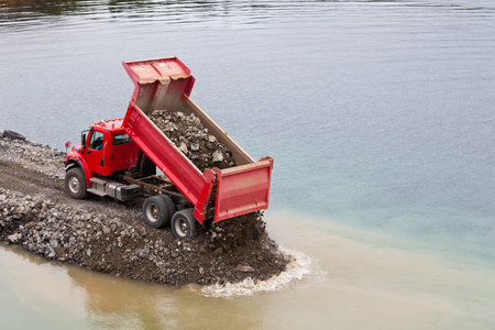 Red dump truck dumping load of soil into water building seawall protecting shoreline and harbor