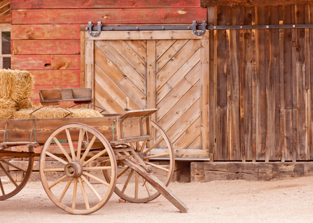 horse cart: Historic horse cart loaded with straw bales standing in front of wooden warehouse wall with door