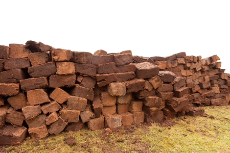 Pile of stacked bog peat turf briquette cuttings left drying in the field