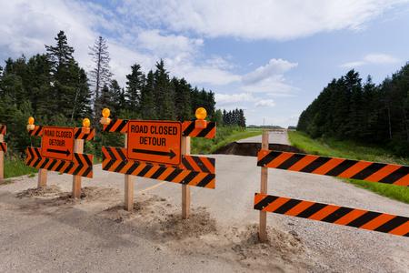 Road closed detour signs on blocked washed out road with rain flood washout damaged broken asphalt Imagens