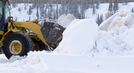 a blizzard: Heavy equipment snow removal after winter snow storm blizzard, loader piling huge amounts of snow Stock Photo