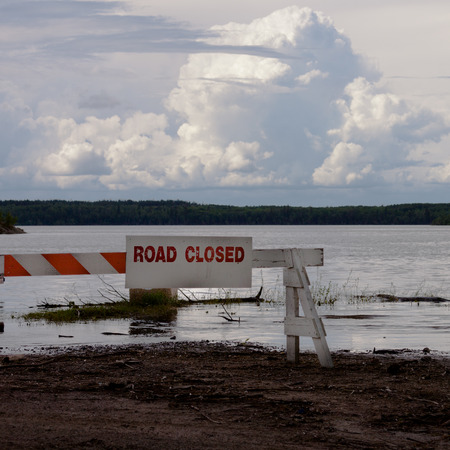 Road closed sign on blocked flooded road with big storm clouds over horizon over flooded area