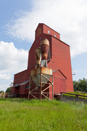 abandoned factory: Historic vintage old grain elevator wooden building structure still standing in the Prairies of Saskatchewan, Canada