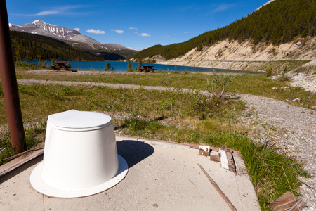 privy: Toilet seat in the open with beautiful view of Summit Lake near Alaska Highway in Stone Mountain Provincial Park, Northern Rockies of British Columbia, Canada Stock Photo