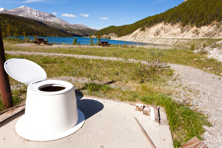rockies: Toilet seat in the open with beautiful view of Summit Lake near Alaska Highway in Stone Mountain Provincial Park, Northern Rockies of British Columbia, Canada Stock Photo