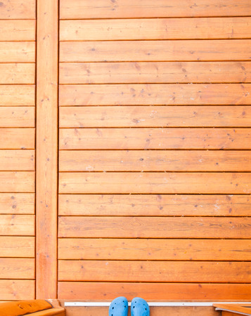 open doorway: Feet in blue rubber shoes in open doorway onto wooden porch or deck from straight above with rich warm wood grain textures and colors Stock Photo