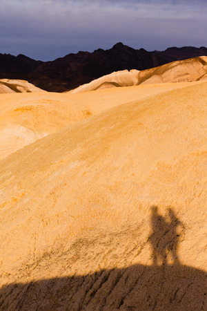 mudstone: Shadow of active couple hiking in colorful shale mudstone badlands of Death Valley National Park, California, USA