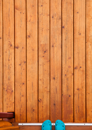 deck: Feet in blue rubber shoes in open doorway onto wooden porch or deck from straight above with rich warm wood grain textures and colors Stock Photo
