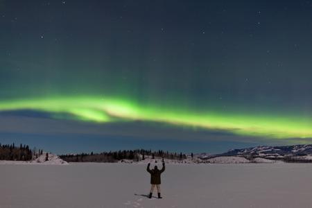 Światła: Człowiek pozdrowienia Northern Lights, Aurora borealis, z podniesionymi rękami w księżyc świeci snowscape z mrożonych Lake Laberge, Yukon Territory, Kanada