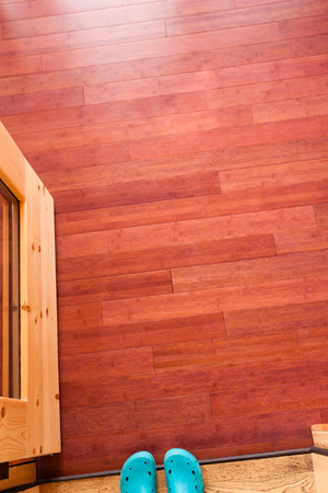 hardwood flooring: Feet in blue rubber shoes in doorway with open glass door leading onto luxury wooden porch shot from above showing rich wood colors and grain textures of porch hardwood flooring