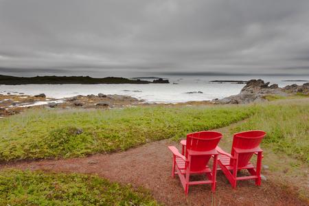 newfoundland: Red Adirondack Chairs overlooking coastal landscape of Newfoundland, NL, Canada