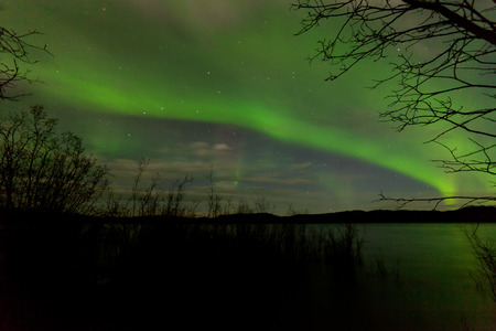 yukon territory: Green band of northern lights, Aurora borealis, over surface of calm lake in Yukon territory, Canada