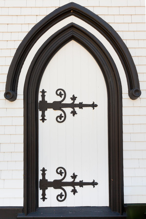 hinged: Black and white wooden door portal entrance doorway entry with artistic wrought iron hinges painted black