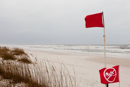 advertencia: Red flags on a Gulf Coast Beach signal swimming in ocean prohibited due to dangerous surf, undercurrent and storm conditions