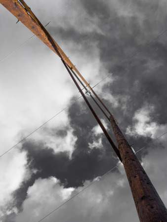 electric line: Wooden poles of high voltage electric power transmission line from right underneath against dramatic cloudy sky Stock Photo