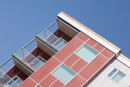angled: Upper corner of modern apartment condominium high rising building stretching angled into blue sky Stock Photo