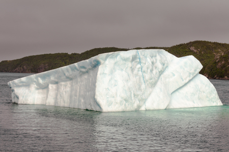 melts: Massive iceberg melts away in coastal waters of Atlantic Ocean off Newfoundland, NL, Canada