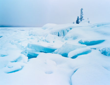 jumbled: Frozen lake shore winter landscape of jumbled ice floes and white snow cover on grey midwinter day Stock Photo